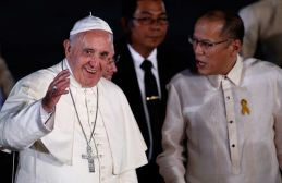 Pope Francis waves to the crowd next to President Aquino upon his arrival at Villamor Air Base in Manila